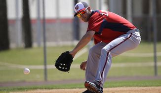 Washington Nationals third baseman Ryan Zimmerman fields a ground ball during a spring training baseball workout Tuesday, Feb. 19, 2013, in Viera, Fla. (AP Photo/David J. Phillip)