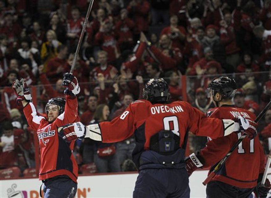 Washington Capitals defenseman Mike Green, left, celebrates his goal with Alex Ovechkin (8), of Russia, and Wojtek Wolski (17), of Poland, during the first period of an NHL hockey game against the Pittsburgh Penguins, Sunday, Feb. 3, 2013, in Washington. (AP Photo/Nick Wass)