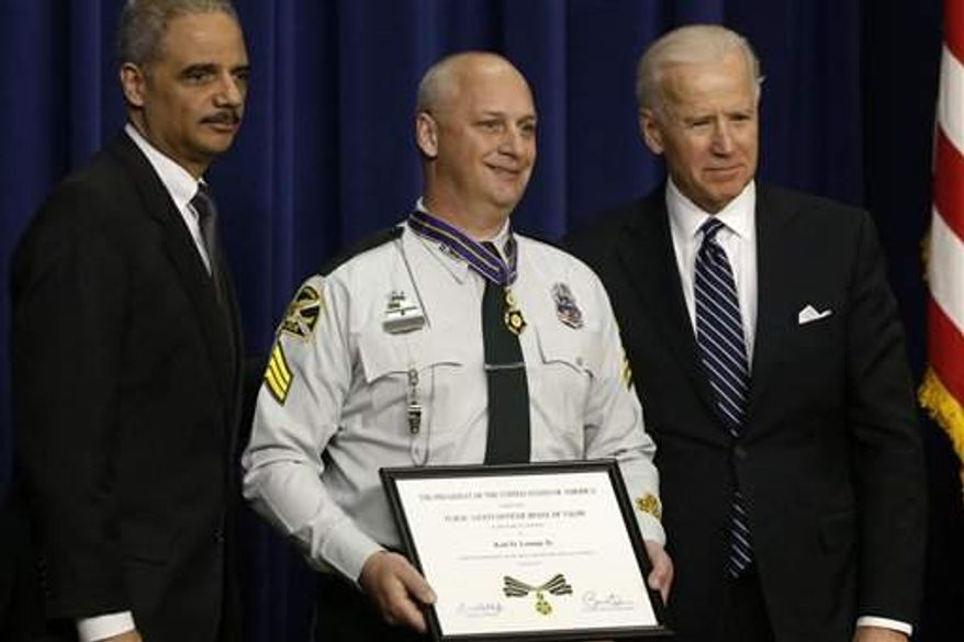 Vice President Joe Biden and Attorney General Eric Holder present the Medal of Valor to St. Petersburg, Fla., Police Sgt. Karl Lounge, Jr., Wednesday, Feb. 20, in the Eisenhower Executive Office Building on the White House complex in Washington. The medal is the highest national award for valor by a public safety officer. (Associated Press)