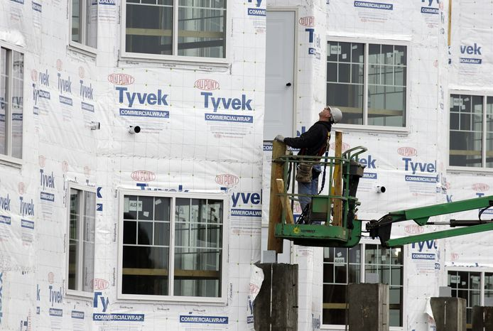 A construction worker checks out at a new home being built in Chicago on Friday, Jan. 11, 2013. (AP Photo/Nam Y. Huh)