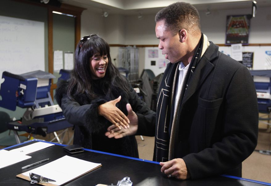 ** FILE ** Then-Rep. Jesse L. Jackson Jr., Illinois Democrat, and his wife, then-Chicago Alderman Sandi Jackson, ask each other for their support and votes as they arrive at a polling station for early voting in Chicago on March 9, 2012. (AP Photo/M. Spencer Green)