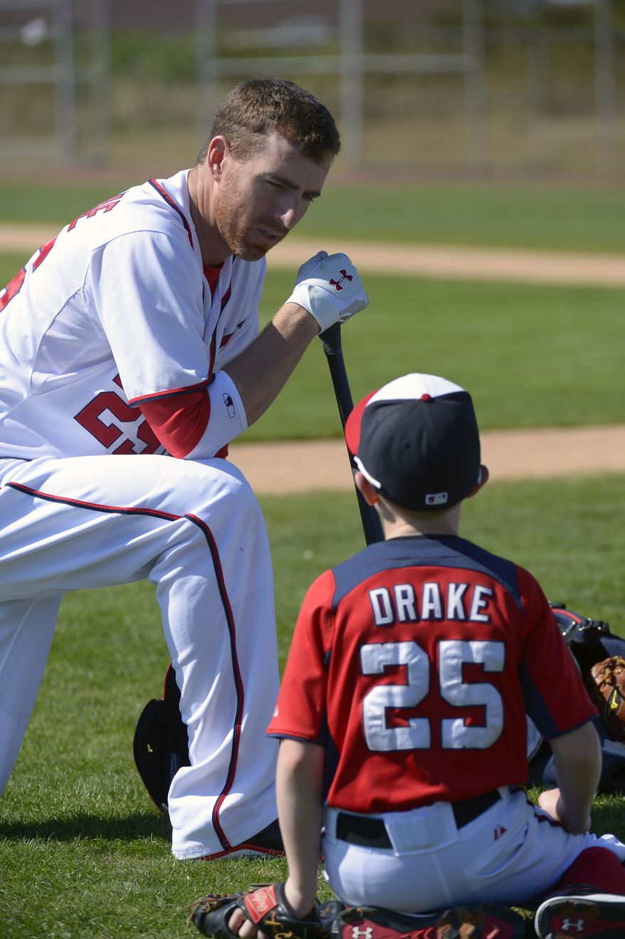 Washington Nationals first baseman Adam LaRoche, left, talks with his son Drake, 11, while waiting to take batting practice during spring training baseball in Viera, Fla., Wednesday, Feb. 20, 2013.(AP Photo/Phelan M. Ebenhack)
