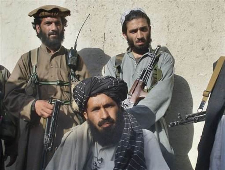 ** FILE ** The commander of a tribal militia, Maulvi Faqir Mohammed center, flanked by his bodyguards, speaks to journalists at Wana, the main town of Pakistan's tribal region of South Waziristan, along the Afghan border.  (Associated Press)