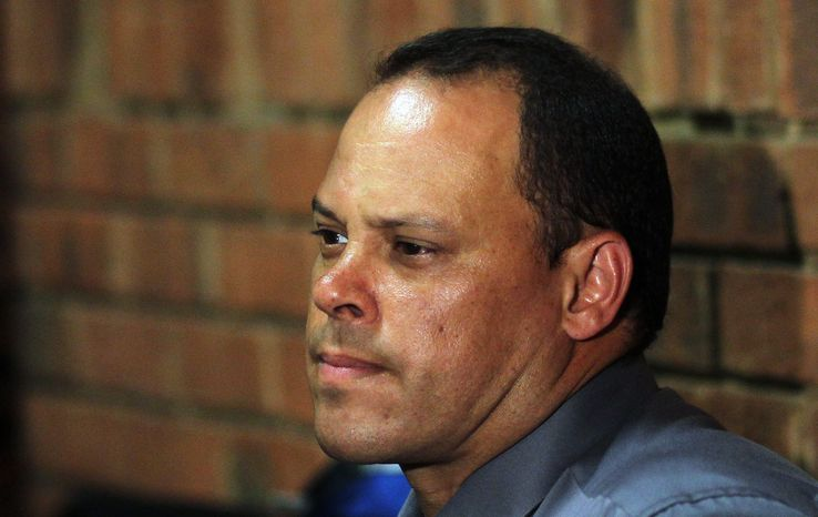 ** FILE ** In this Wednesday, Feb. 20, 2013, file photo, investigating officer Hilton Botha, sits inside the court witness box during the Oscar Pistorius bail hearing at the magistrate court in Pretoria, South Africa. The lead investigator in the murder case against Oscar Pistorius faces attempted murder charges himself over a 2011 shooting, police said Thursday, Feb. 21, 2013, in another potentially damaging blow to the prosecution. (AP Photo/Themba Hadebe, File)