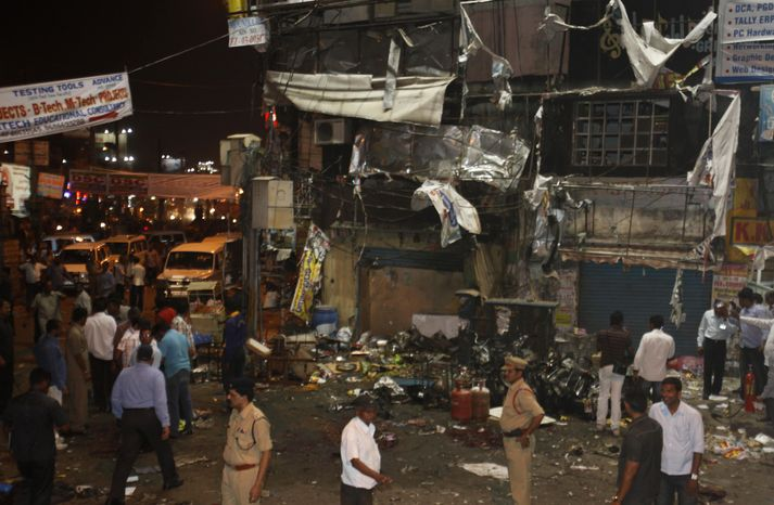 People and police officers stand at the spot of a bomb blast in Hyderabad, India, on Feb. 21, 2013. A pair of bombs exploded in a crowded shopping area, killing several people and wounding many in the worst bombing in the country in more than a year, officials said. (Associated Press)