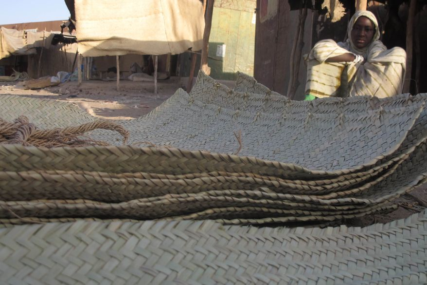 In this Wednesday, Feb. 20, 2013, photo, a young vendor waits for clients alongside woven reed mats of the type purchased by fleeing Islamists, apparently to camouflage their vehicles, in Timbuktu, Mali. (AP Photo/Rukmini Callimachi)