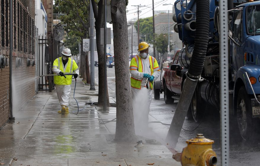 **FILE** Sanitation workers in a protective suits clean a street in the heart of the Skid Row district in downtown Los Angeles on June 20, 2012. The three-week cleanup that started this week will get rid of rats' nests, hypodermic needles, condoms, human excrement and other hazards. Weekly inspections will follow. A federal court injunction last year placed limits on the removal of unattended items, but doesn't prevent removal of items that pose health risks. (Associated Press)