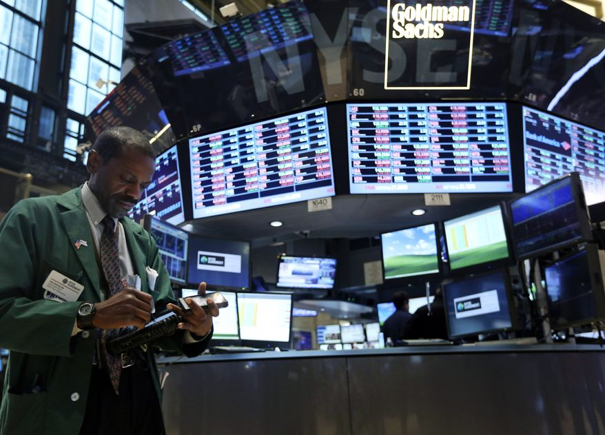 **FILE** A trader works Feb. 21, 2013, on the floor of the New York Stock Exchange. (Associated Press)
