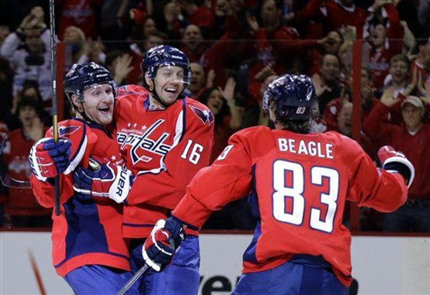 Washington Capitals defenseman Karl Alzner (27) celebrates with right wing Eric Fehr (16) as center Jay Beagle (83) comes to join in after Fehr's goal in the third period of an NHL hockey game against the New Jersey Devils Saturday, Feb. 23, 2013 in Washington. The Capitals won 5-1. (Associated Press)