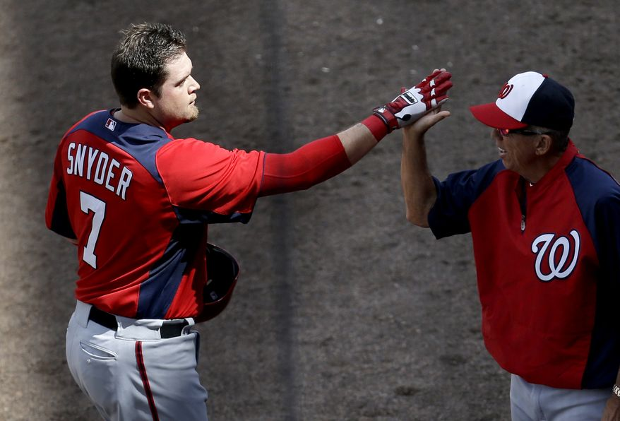 Washington Nationals catcher Chris Snyder, left, is congratulated by manager Davey Johnson after hitting a home run off New York Mets pitcher Shaun Marcum during the second inning of an exhibition spring training baseball game in Port St. Lucie, Fla., Saturday, Feb. 23, 2013, in (AP Photo/Julio Cortez)