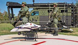 SWAT team members are posted next to a ShadowHawk drone in Texas. Worried about violations of civil liberties, at least 19 states are considering limits on how the unmanned craft can be used. (Vanguard Defense Industries via Associated Press)