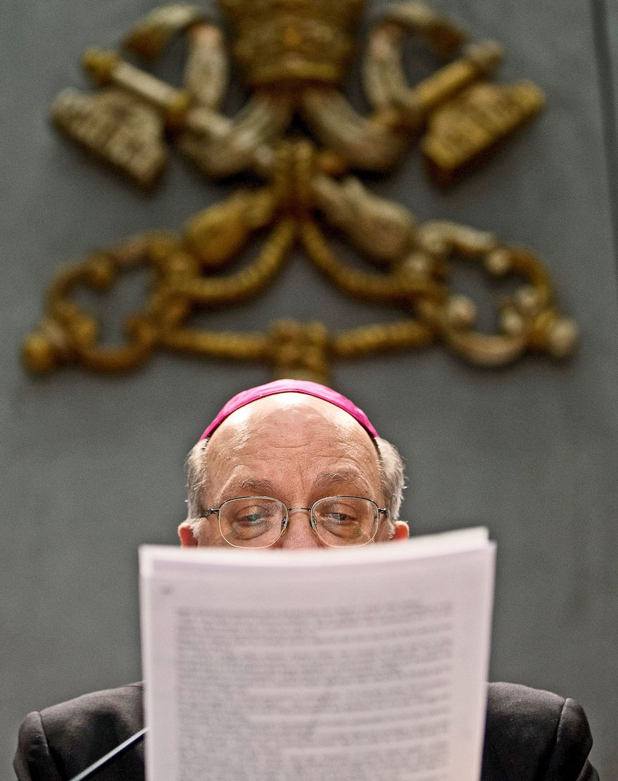 Archbishop Pier Luigi Celata reads a copy of a document signed by Pope Benedict XVI changing the rules of the conclave. (Associated Press)