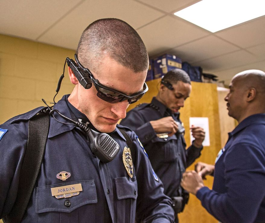 Laurel Police Deputy Chief James Brooks (right) helps Officer Carl Johnson in the proper way to wear a new Taser Axon Flex camera. Officer Matthew Jordan (left) is wearing one of the cameras. (Andrew S. Geraci/The Washington Times)