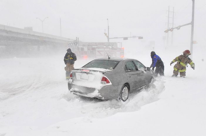 Amarillo emergency personnel assisted a stranded motorist on the I-40 service road Monday, Feb. 25, 2013. A blizzard packing 50 mph wind gusts and more than 11 inches of snow blasted Amarillo and Texas Panhandle Monday, Feb. 25, 2013, making travel nearly impossible. Interstate 40 and many major highways in the Panhandle have been closed. (AP Photo/The Amarillo Globe News,Michael Schumacher)
