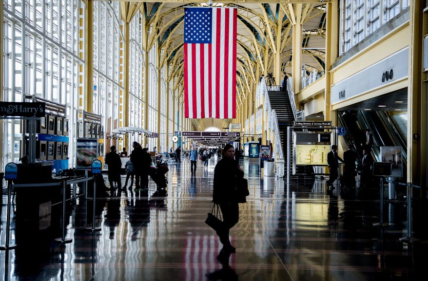 An U.S. flag hangs from the rafters at Reagan National Airport in Washington on Feb. 25, 2013, as travelers pass through. (Andrew S. Geraci/The Washington Times)