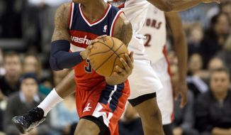 Toronto Raptors guard Alan Anderson, rear, defends against Washington Wizards guard Bradley Beal (3) during the first half of their NBA basketball game, Monday, Feb. 25, 2013, in Toronto. (AP Photo/The Canadian Press, Frank Gunn)