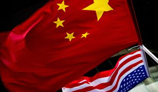 U.S. and Chinese national flags are hung outside a hotel Nov. 7, 2012, during a U.S. Presidential election event, organized by the U.S. Embassy in Beijing. (Associated Press) ** FILE **