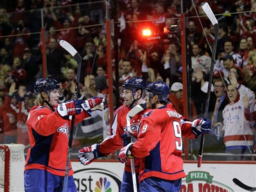 Washington Capitals center Nicklas Backstrom, left, from Sweden, right wing Troy Brouwer (20) and center Mike Ribeiro (9) celebrate Backstrom's goal in the first period of an NHL hockey game against the Carolina Hurricanes on Tuesday, Feb. 26, 2013, in Washington. (AP Photo/Alex Brandon)