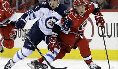 Carolina Hurricanes' Alexander Semin (28) and Winnipeg Jets' Alex Burmistrov (8), both of Russia, struggle for possession of the puck during the first period of an NHL hockey game in Raleigh, N.C., Thursday, Feb. 21, 2013. (AP Photo/Gerry Broome)