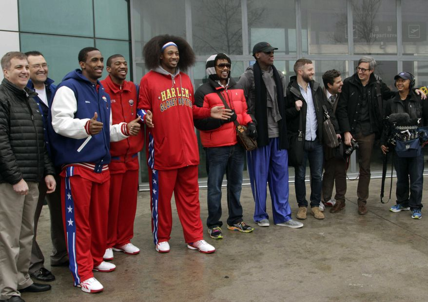 """Flamboyant former NBA star Dennis Rodman (fifth from right) poses with three members of the Harlem Globetrotters basketball team (in red jerseys) and a media production crew upon their arrival at the Pyongyang airport in North Korea on Tuesday, Feb. 26, 2013. Rodman, known as """"The Worm,"""" is an unlikely ambassador for sports diplomacy at a time of heightened tensions between the U.S. and North Korea. (AP Photo/Kim Kwang Hyon)"""