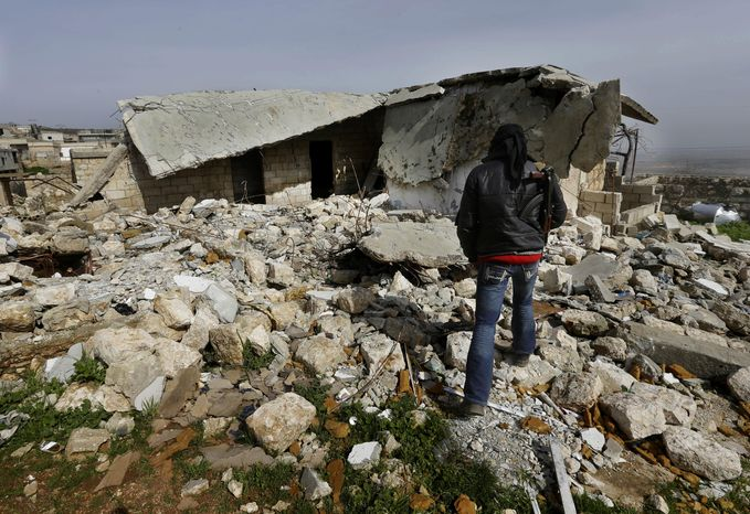 A Free Syrian Army fighter walks on rubble of a base destroyed from a Syrian forces airstrike, at Jabal al-Zaweya village of Sarjeh, in Idlib, Syria, Monday Feb. 25, 2013. (AP Photo/Hussein Malla)