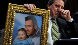 Neil Heslin holds a picture of himself and his young son Jesse, who was 6 when he was killed at Sandy Hook Elementary, while testifying Wednesday before the Senate Judiciary Committee on the Assault Weapons Ban of 2013. (Associated Press)