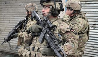 ** FILE ** U.S. soldiers stand guard at the scene of a suicide attack in Kabul, Afghanistan, Wednesday, Feb. 27, 2013. (AP Photo/Musadeq Sadeq)