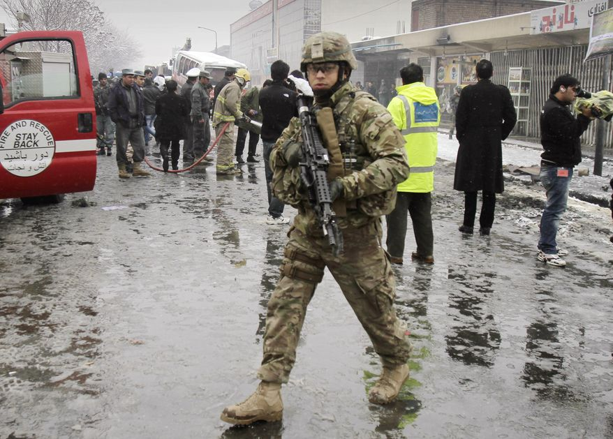 A U.S. soldier with the NATO forces patrols at the scene of a suicide attack in Kabul, Afghanistan, on Wednesday, Feb. 27, 2013. A man wearing a black overcoat and carrying an umbrella as a shelter against the heavy snow crossed a street in the Afghan capital toward an idling bus filled with Afghan soldiers, where he lay down and wiggled underneath. Then an explosion engulfed the undercarriage of the bus in flames. (AP Photo/Ahmad Jamshid)