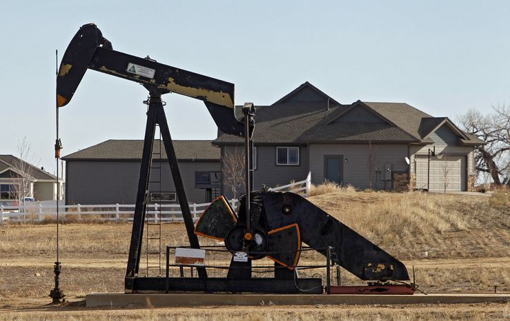 This photo taken on Thursday, Jan. 19, 2012, near Frederick, Colo., shows an oil pump jack working on a property across from a subdivision. Colorado that week passed what it touted as one of the toughest statewide regulations of energy drilling in the nation, a sign of a growing backlash against an oil and gas boom that has moved from far-flung rural areas to densely-populated urban ones. The state's new regulations require a 500-foot setback from houses for all new energy projects and other regulations geared toward areas like the Denver suburbs that are increasingly being targeted for natural gas and oil drilling. (AP Photo/Ed Andrieski)