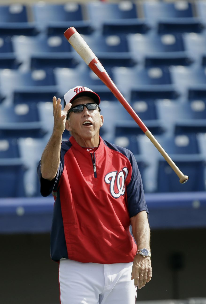 Washington Nationals manager Davey Johnson tosses his bat while hitting ground balls to first baseman Adam LaRoche before an exhibition spring training baseball game against the Miami Marlins Wednesday, Feb. 27, 2013, in Viera, Fla. (AP Photo/David J. Phillip)