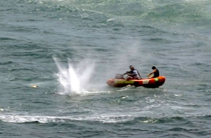 "Police in inflatable rubber boats shoot at a shark off Muriwai Beach near Auckland, New Zealand, Wednesday, Feb. 27, 2013, as they attempt to retrieve a body following a fatal shark attack. Police said a man was found dead in the water after being ""bitten by a large shark."" (AP Photo/Ross Land)"