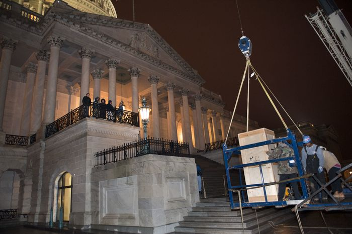 Riggers load a crate containing the bronze statue of Rosa Parks onto a basket suspended from a crane as it is delivered to the U.S. Capitol's Memorial Door, in Washington, Friday, Feb. 22, 2013, where it will join the U.S. Capitol Art Collection. Authorized by Public Law 109-116, as modified by Public Law 110-120, the Rosa Parks statue represents the first commission of a full-sized statue approved and funded by the U.S. Congress since 1873. It will be installed in National Statuary Hall in the United States Capitol on Feb. 27, 2013. (AP Photo/Cliff Owen)