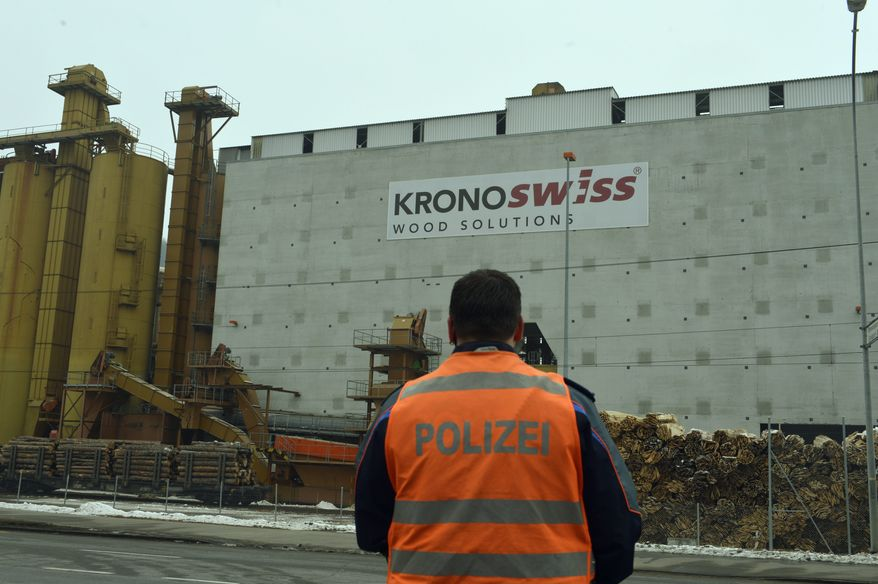 A policeman stands in front of a wood-processing company in Menznau, Switzerland, where several people were killed in a shooting on Wednesday, Feb. 27, 2013. (AP Photo/Keystone, Urs Flueeler)