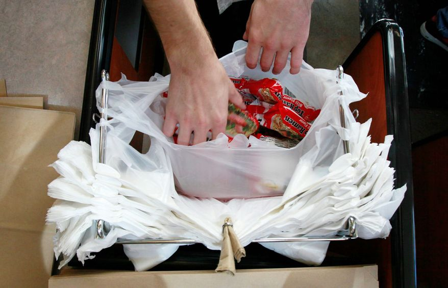 **FILE** A clerk bags groceries in plastic bags at the M Street Grocery in Seattle on Aug. 3, 2009. (Associated Press)