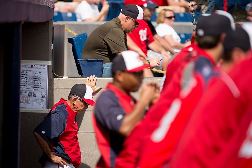 Washington Nationals general manager Mike Rizzo, top, and Washington Nationals manager Davey Johnson (5), bottom left, as the Washington Nationals play the Florida Marlins during spring training at Space Coast Stadium, Viera, Fla., Wednesday, February 27, 2013. (Andrew Harnik/The Washington Times)