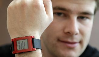Eric Migicovsky, CEO of Pebble, displays his company's smart watch in Palo Alto, Calif., Tuesday, Feb. 12, 2013. This new watch not only tells time, but also connects to smart phones within 10 meters. (AP Photo/Marcio Jose Sanchez)