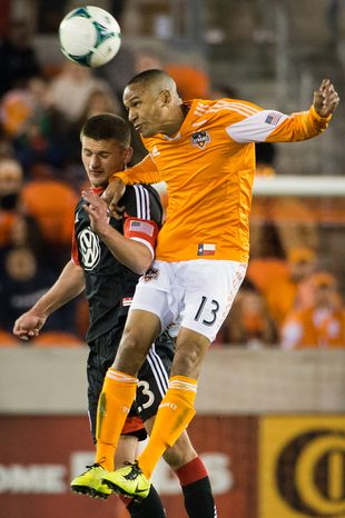 Houston Dynamo midfielder Ricardo Clark (13) wins a header from D.C. United midfielder Perry Kitchen (23) during the first half of an MLS soccer match Saturday, March 2, 2013, in Houston. (AP Photo/Houston Chronicle, Smiley N. Pool)