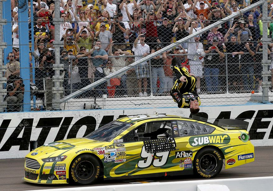 Carl Edwards celebrates winning the NASCAR Sprint Cup Series auto race, Sunday, March 3, 2013, in Avondale, Ariz. (AP Photo/Matt York)
