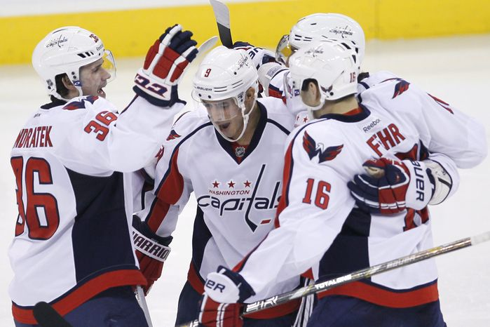 Washington Capitals' Tomas Kundratek (36), Mike Ribeiro (9), Alex Ovechkin (8) and Eric Fehr (16) celebrate Ribeiro's goal against the Winnipeg Jets during third-period NHL hockey game action in Winnipeg, Manitoba, Saturday, March 2, 2013. (AP Photo/The Canadian Press, John Woods)