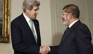 U.S. Secretary of State John F. Kerry (left) shakes hands with Egyptian President Mohammed Morsi at the Presidential Palace in Cairo on Sunday, March 3, 2013. Mr. Kerry is wrapping up a visit to the deeply divided country with an appeal for unity and reform. The United States is deeply concerned that continued instability in Egypt will have broader consequences in a region already rocked by unrest. (AP Photo/Jacquelyn Martin, Pool)