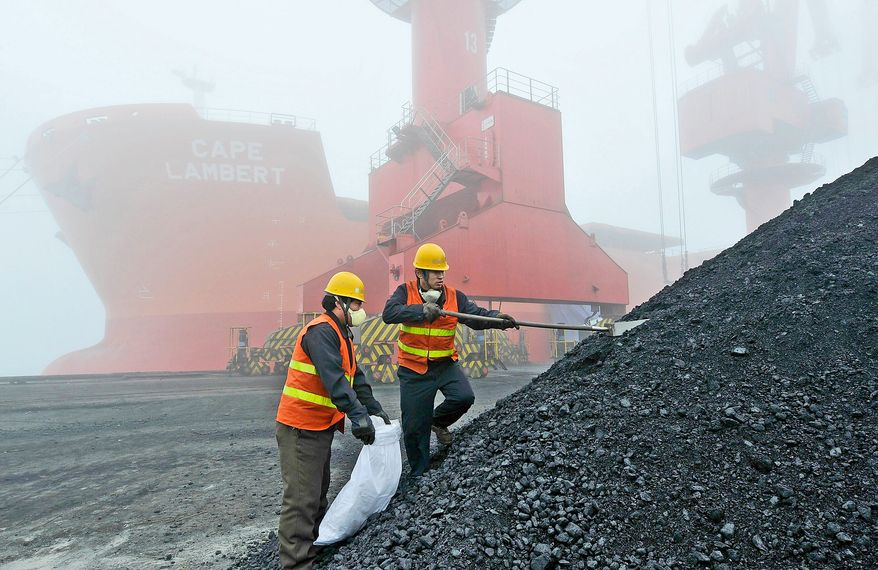 Officers of the Entry-Exit Inspection and Quarantine Bureau fetch coal sample for test at the coal dock of Rizhao Harbor in Rizhao in China's Shandong province on Wednesday, Feb. 24, 2010. China, the largest producer of coal in the world, became a net coal importer in 2009 as the country imported 130 million tons of coal last year, almost twice the volume for 2008. Its coal output reached 2.96 billion tons in 2009, up 12.7 percent year-on-year.(Photo By Chen Weifeng/Color China Photo/AP Images)