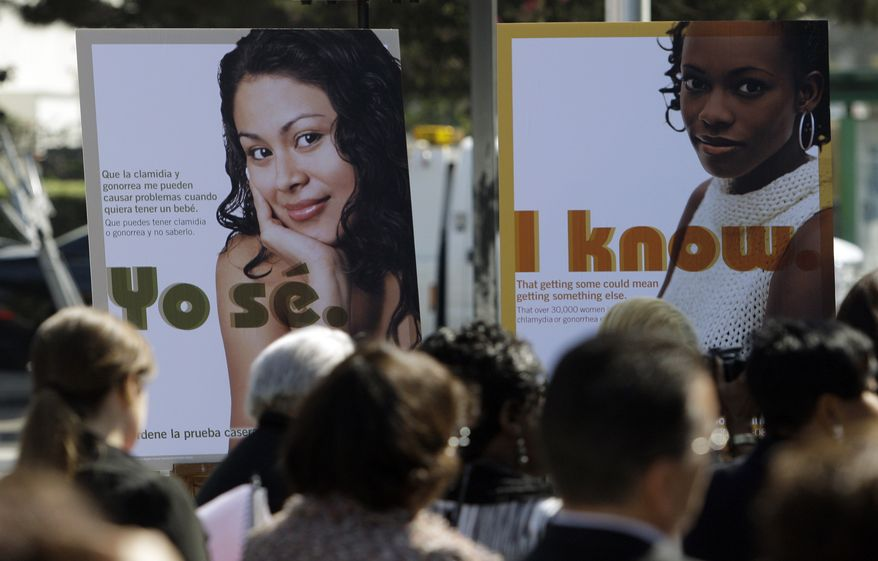 ** FILE ** Public service posters in English and Spanish are seen at a news conference to announce a Los Angeles County program to provide young women in South Los Angeles with home-testing kits for sexually transmitted diseases, at a news conference in the Watts-Willowbrook area of Los Angeles on Sept. 19, 2011. Los Angeles County has the highest number of chlamydia cases and the second-highest number of gonorrhea cases in the country. (Associated Press)