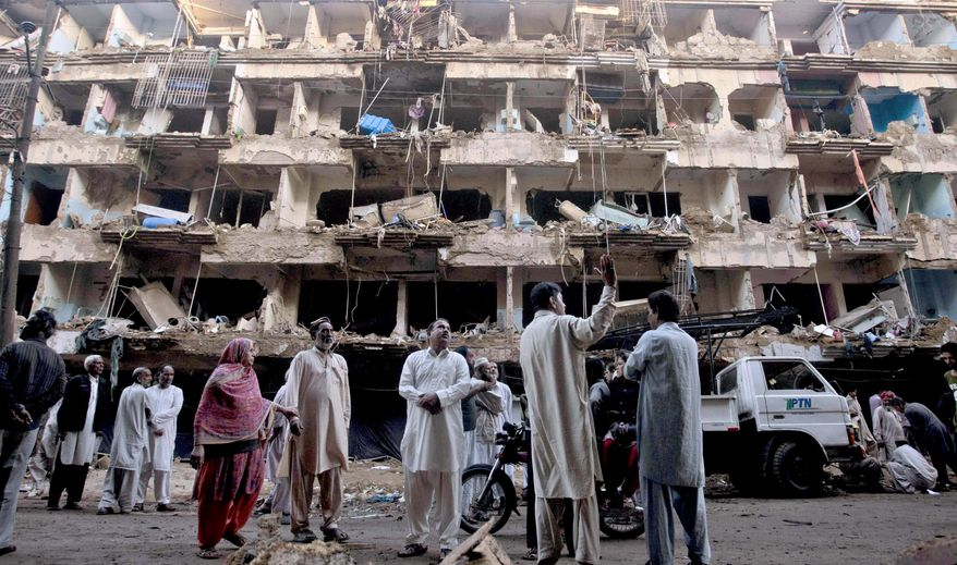 Pakistanis gather at the site of Sunday's car bombing in Karachi, Pakistan, Monday, March 4, 2013. Members of Pakistan's Shiite community were digging Monday through the rubble of the massive car bombing in Karachi looking for loved ones. (AP Photo/Shakil Adil)