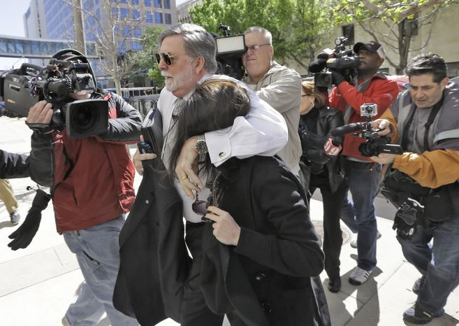 Casey Anthony is protected from the media by her attorney, Cheney Mason, as she arrives at the U.S. Courthouse in Tampa, Fla., for a bankruptcy hearing on Monday, March 4, 2013. Ms. Anthony has not been seen in public since being acquitted in 2011 of murdering her 2-year-old daughter, Caylee. (AP Photo/Chris O'Meara)