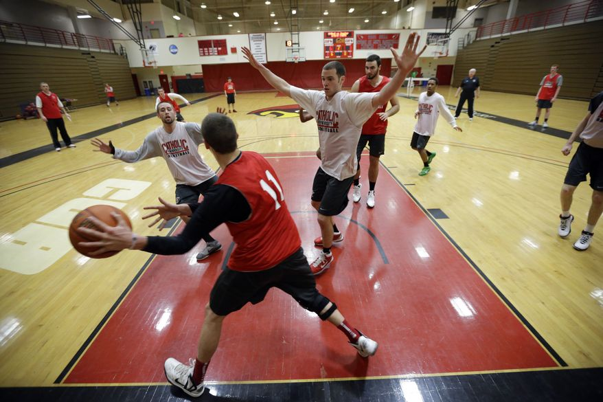 In this photo taken Feb. 12, 2013, Catholic University players workout during an NCAA college basketball practice in Washington. The men's and women's teams at the Division III school are have a combined record of 42-4. (AP Photo/Alex Brandon)