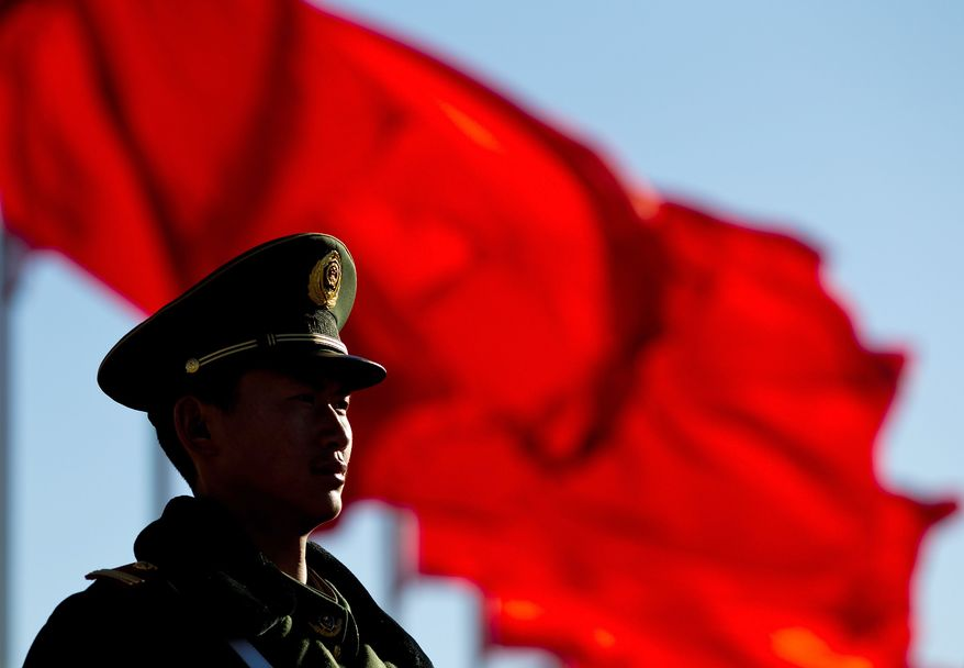 A Chinese paramilitary policeman stands guard on Tiananmen Square while sessions of the National People's Congress and the Chinese People's Political Consultative Conference are held at the Great Hall of the People in Beijing Monday, March 4, 2013. (AP Photo/Andy Wong)
