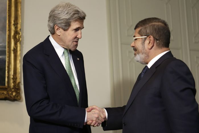 U.S. Secretary of State John Kerry (left) shakes hands with Egyptian President Mohamed Morsi at the Presidential Palace in Cairo on March 3, 2013. (Associated Press)