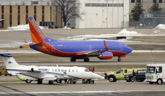 Emergency vehicles surround an aircraft (bottom) that sits on the tarmac after making an emergency landing as another jet takes off at Lambert St. Louis International Airport on March 4, 2013. An official says the eight passengers aboard the small aircraft with landing gear troubles walked off the plane after it landed safely. (Associated Press)