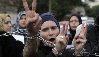 ** FILE ** Palestinians and foreign activists chant slogans as they march with their hands chained together during a protest held in solidarity with Palestinian prisoners held in Israeli jails in Gaza City, Thursday, Feb. 14, 2013. (AP Photo/Adel Hana)