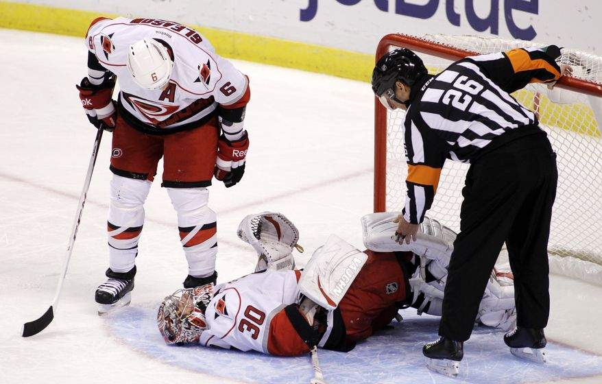 Carolina Hurricanes' Tim Gleason (6) and referee Rob Martell (26) talk to goalie Cam Ward (30) after an injury during the second period of an NHL hockey game against the Florida Panthers, Sunday, March 3, 2013, in Sunrise, Fla. Ward was helped off the ice and did not return to the game. (AP Photo/Luis M. Alvarez)